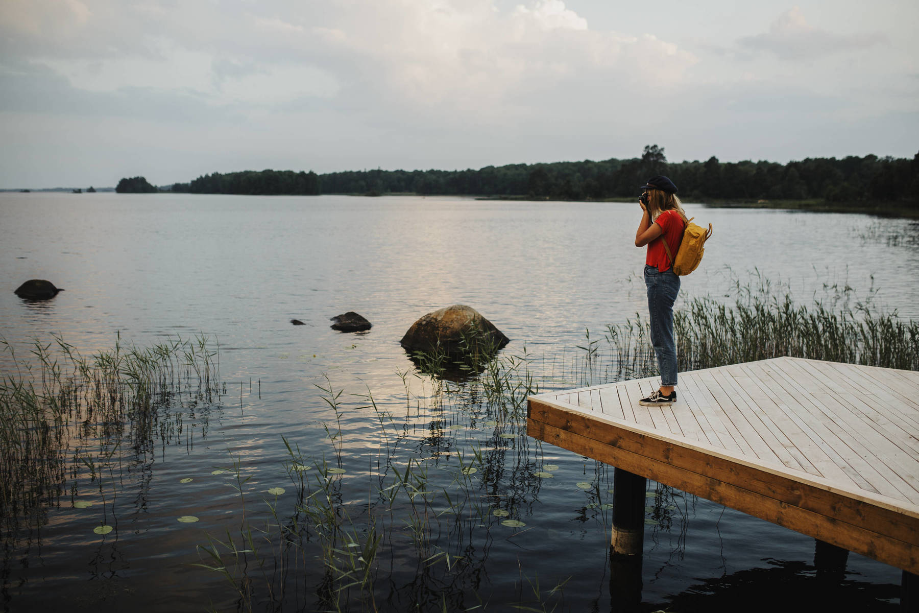 Woman on the wooden deck by lake Åsnen in Åsnen National Park
